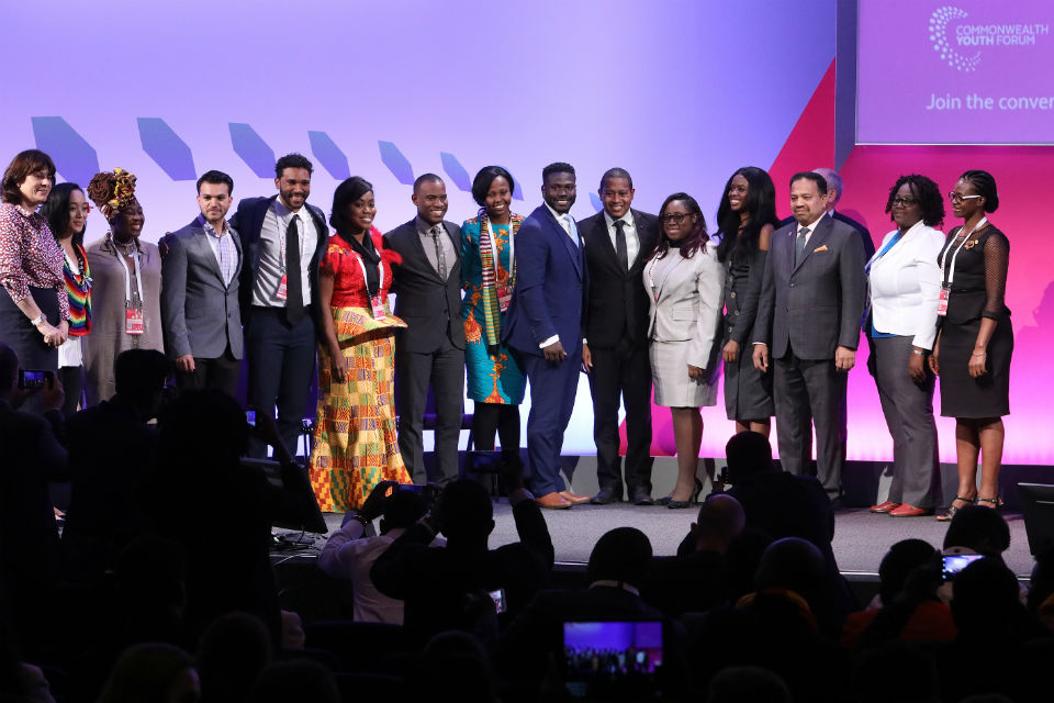 Group of men and women standing on stage at conference