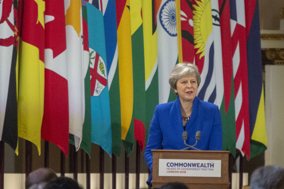 Woman speaking at lectern in front of national flags