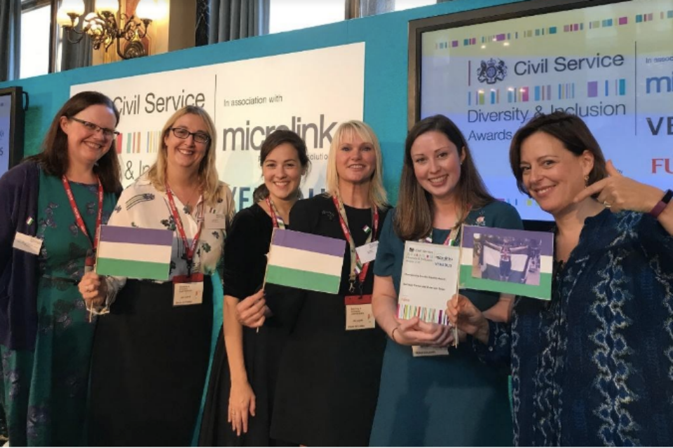Members of the Suffrage Centenary Volunteer Team at the Foreign and Commonwealth Office awards ceremony, with their award for winning the Championing Gender Equality category in the 2018 Civil Service Diversity and Inclusion Awards; and (right) award presenter Melanie Dawes, Civil Service Gender Champion
