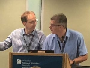 Two men at lectern during conference