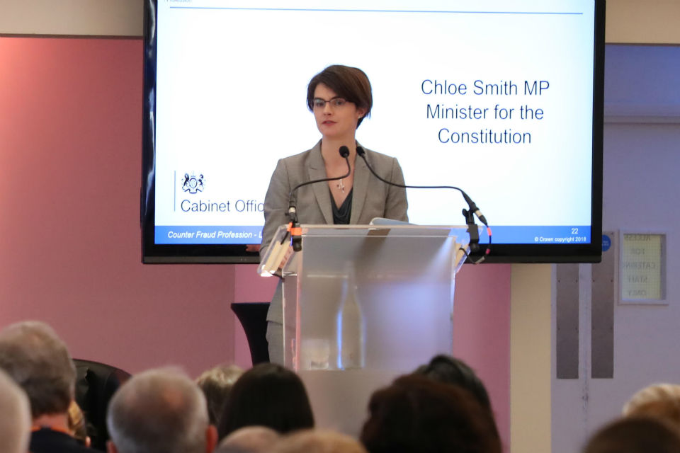 Chloe Smith speaking from a lectern at an event