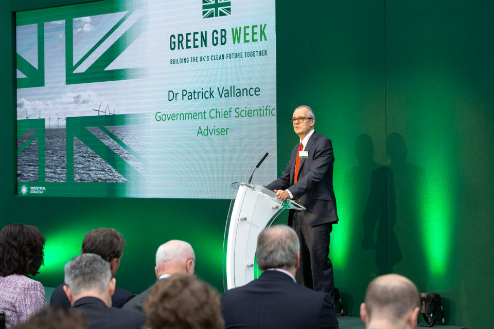 Dr Patrick Vallance speaking from the stage at the Green GB Week, Building the UK's Clean Future Together, event, in front of a green backdrop and the projection of the event title and his name.