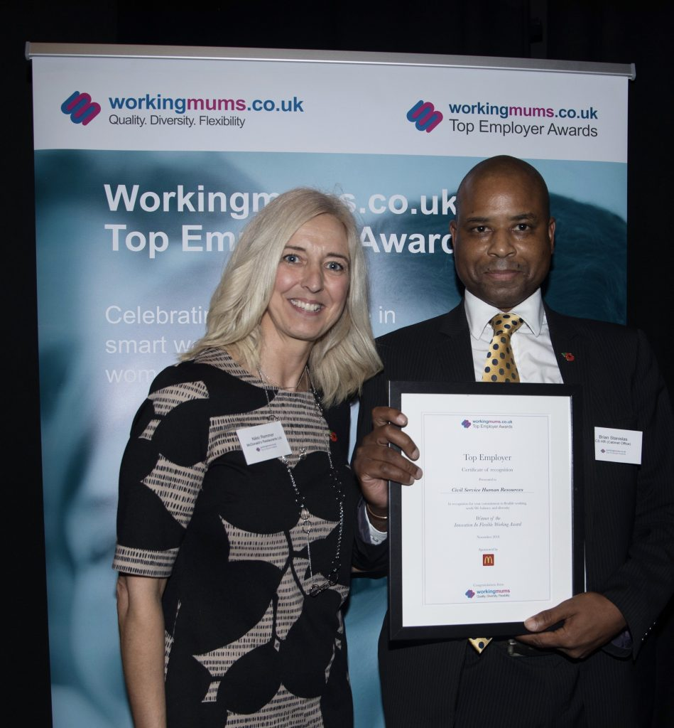 Man holding up framed award certificate next to female presenter