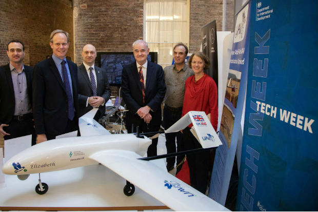Dr Gavin Smith, Matthew Rycroft CBE, Daniel Ronen, Dr Joseph Barnard, Alex Caccia, and Professor Charlotte Watts beside a prototype of an aid-delivering drone at DFID Whitehall Occasion: Unmanned Aerial Vehicles (UAVs) display for staff. Three British UAV innovators and a British data analysis unit showed staff their technology and pilot projects with DFID.