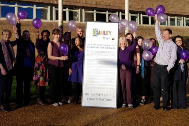 Group of civil servants holding up purple balloons and flanking a board with details of the Global Disability Summit Charter for Change