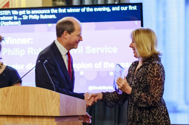 Philip Rutnam, left, receiving his Business Disability Forum Disability Smart Award for Senior Disability Champion of the Year on the stage at the awards ceremony