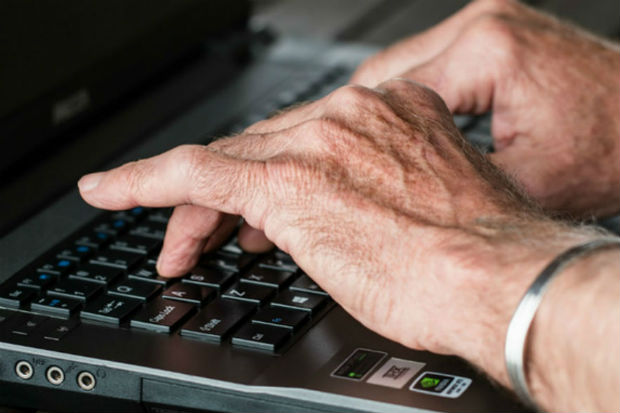 Image showing a man's hands typing on the keyboard of a laptop computer.