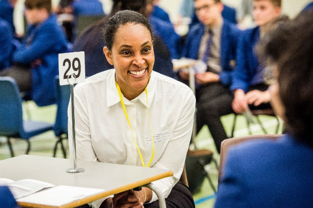 Michele Anderson sitting at a table and speaking to school students at an outreach event on social mobility