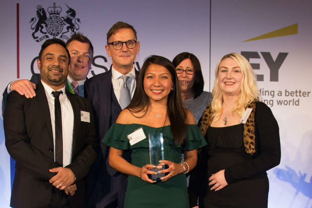 Members of Team Chaffinch with presenter Jonathan Jones on the stage at the 2018 Civil Service Awards, one of them holding the award.