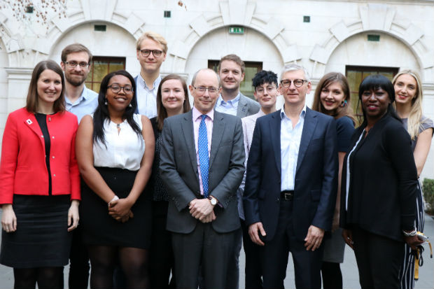 A group of men and women members of the Geospatial Commission, including its new chair, Sir Andrew Dilnot, standing in the courtyard of a government department