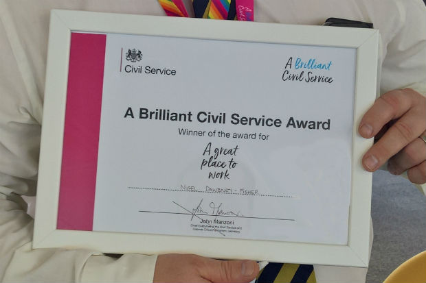 Hands holding the framed certificate of 'A Brilliant Civil Service' Award for 'A great place to work'