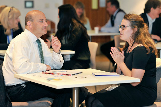 A man and a woman deep in conversation at a spot mentoring session at a Civil Service Live event, seated at a table, with others in conversation at tables in the background