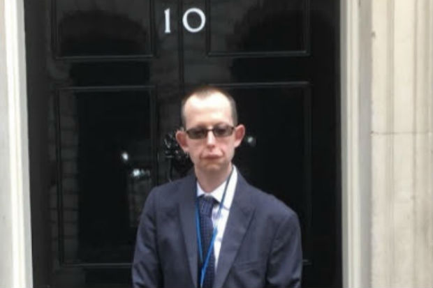 Photograph of Andrew Wight standing outside the door of No. 10 Downing Street