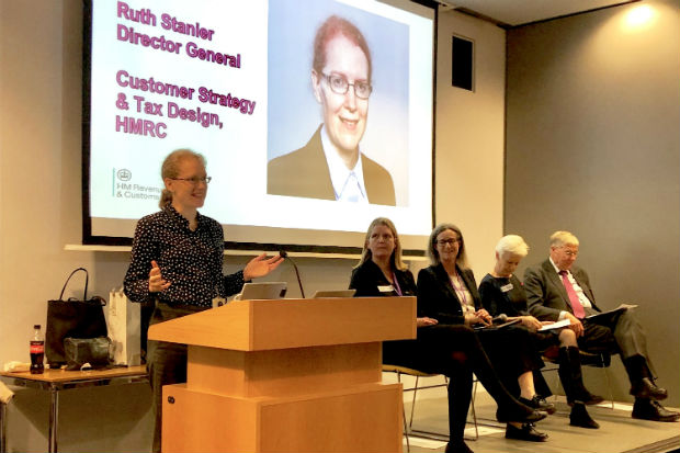 Ruth Stanier speaking at lectern with screen behind showing her picture, name and title, and a group of three women and a man seated alongside her on a platform