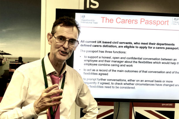 Brian Day speaking at a cross-government carers event in front of a screen containing infromation about the Carer's Passport