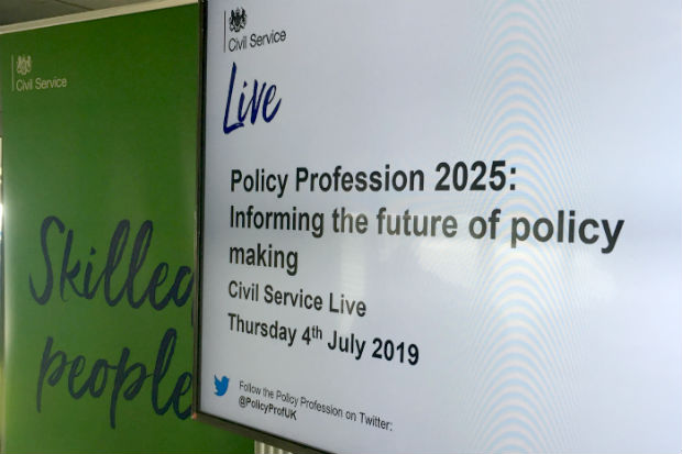 View of a display screen on the stand of the Civil Service Policy Profession at Civil Service Live, showing the text: Policy Profession 2025: Informing the future of policy making, Civil Service Live, Thursday, 4th July 2019