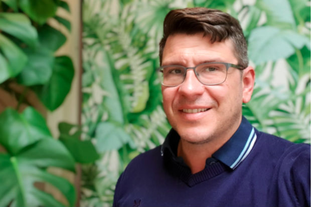 Head and shoulders of bespectacled Paul Morrison, standing in front of a rubber plant and wallpaper with a pattern of tropical green plant leaves