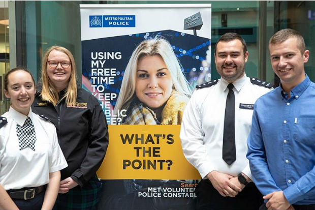 Special constables standing beside a banner promoting special constable roles in the Metropolitan Police
