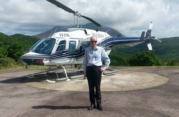 Ben Merrick on a helicopter landing pad in Montserrat, with a helicopter behind him