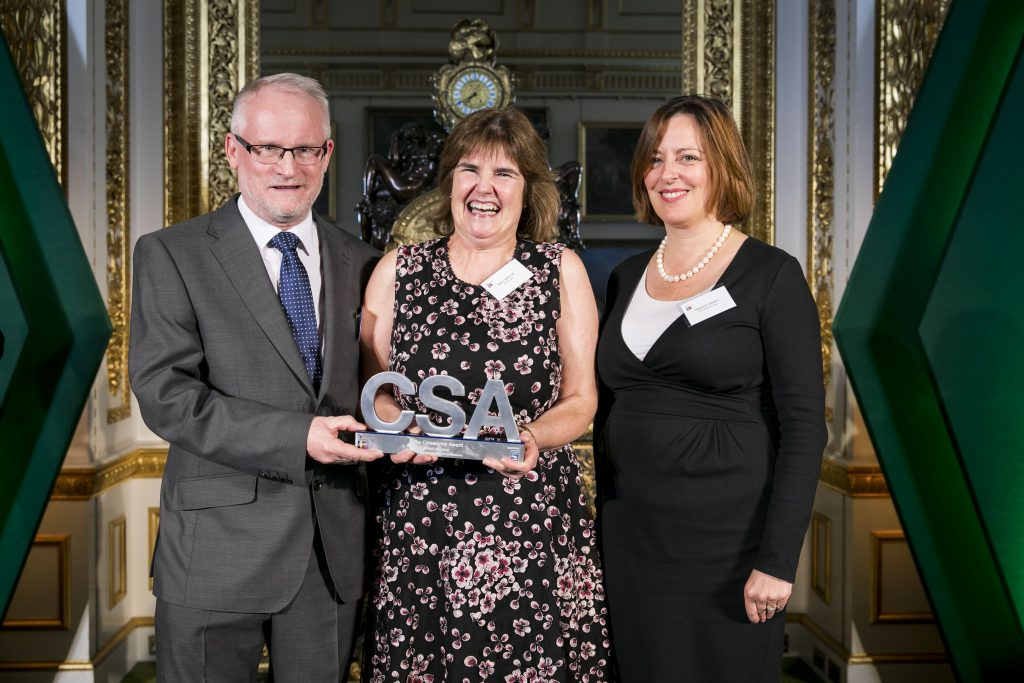 Mairi Macneil, holding her Citizenship Award, flanked by two award presenters