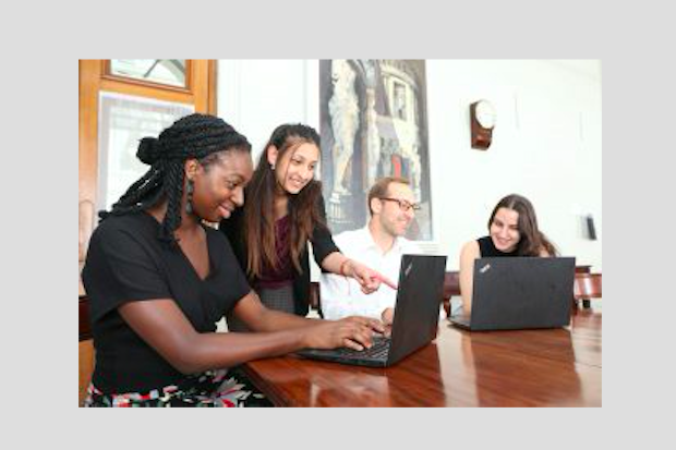 A group of four young people around a table and looking at laptops