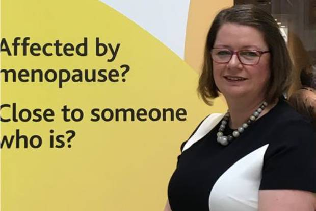 Karen Canner in front of a banner displaying the words: Affected by menopause? Close to someone who is?