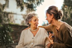 Young woman carer helping older woman