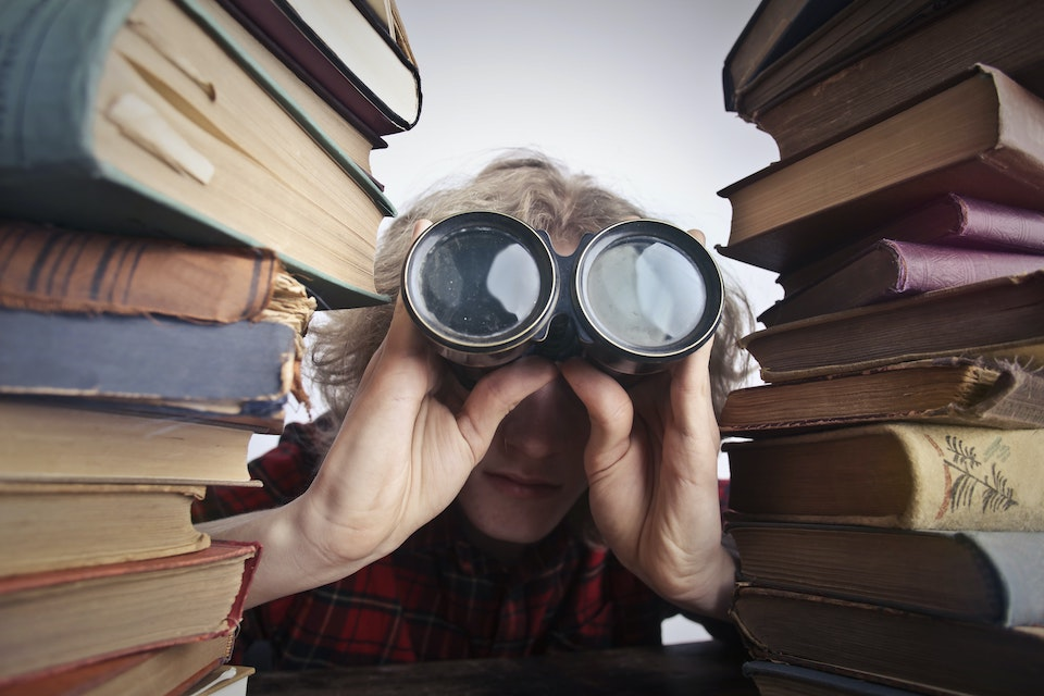 Image of a woman looking through binoculars next to pile of books